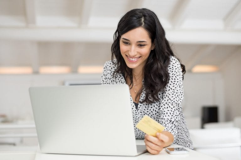 Happy,Young,Woman,Holding,A,Credit,Card,And,Shopping,Online
